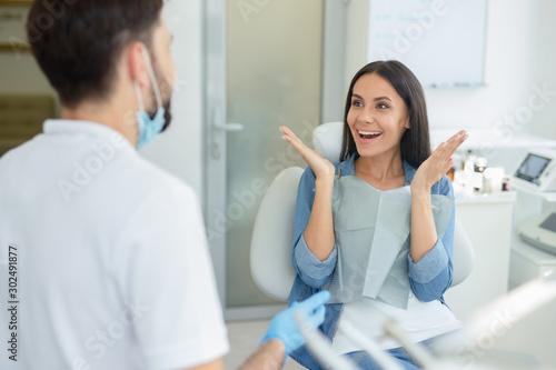 Fotografiet  woman gesturing near dentist talking to her in clinic