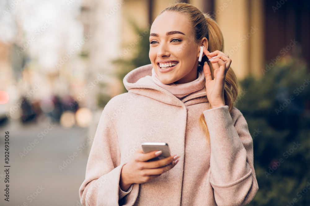Fototapeta Millennial woman enjoying music in airpods, walking in city