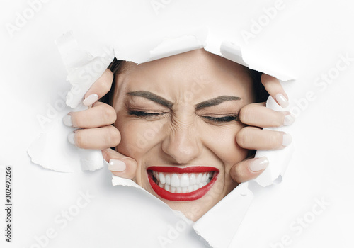 Fotografía Young beautiful woman is struggling to break through a white material wall