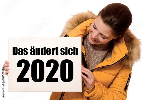 Fröhliche junge Frau hält Schild: Das ändert sich 2020 Fototapet