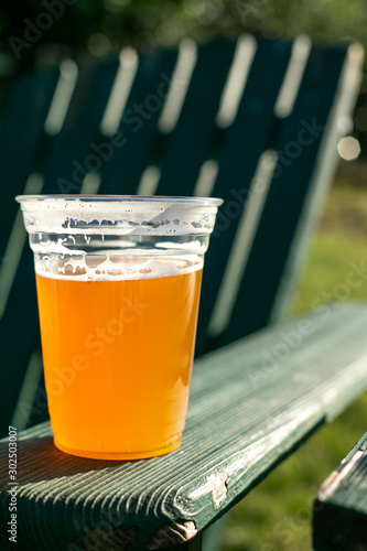 Beer in a plastic cup on the armrest of a lawn chair Canvas Print