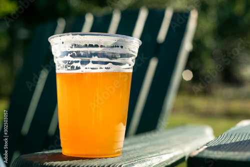 Beer in a clear plastic cup, on the armrest of a patio chair Canvas Print