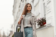 canvas print picture - Elegant young woman is walking in a stylish trench coat with a black handbag in a warm knitted sweater near vintage buildings with flowers on the facades.Attractive lady enjoys a walk on a city street