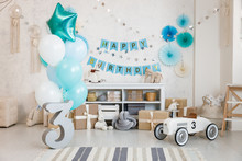 Birthday Decorations With Gifts, Toys, Balloons, Garland And Figure 3 For Little Baby Party On A White Wall Background.