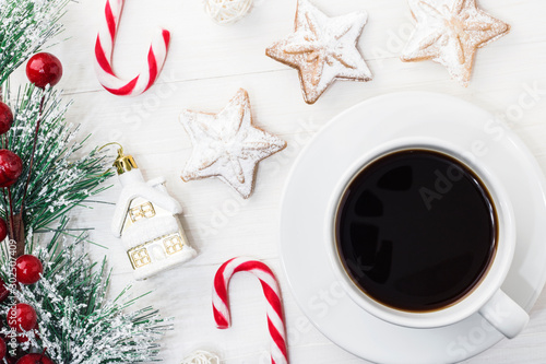 Foto op Aluminium Cafe A white mug of black Americano coffee with Spruce branch tree on a white wooden background next to Christmas cookies, a candy cane and New Year's toys. Copy space. Top view.