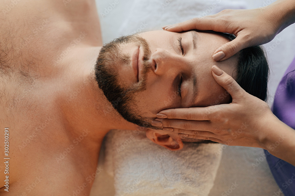 Fototapeta Handsome man relaxing with eyes closed during head massage at wellness resort. Massage head pain treatment