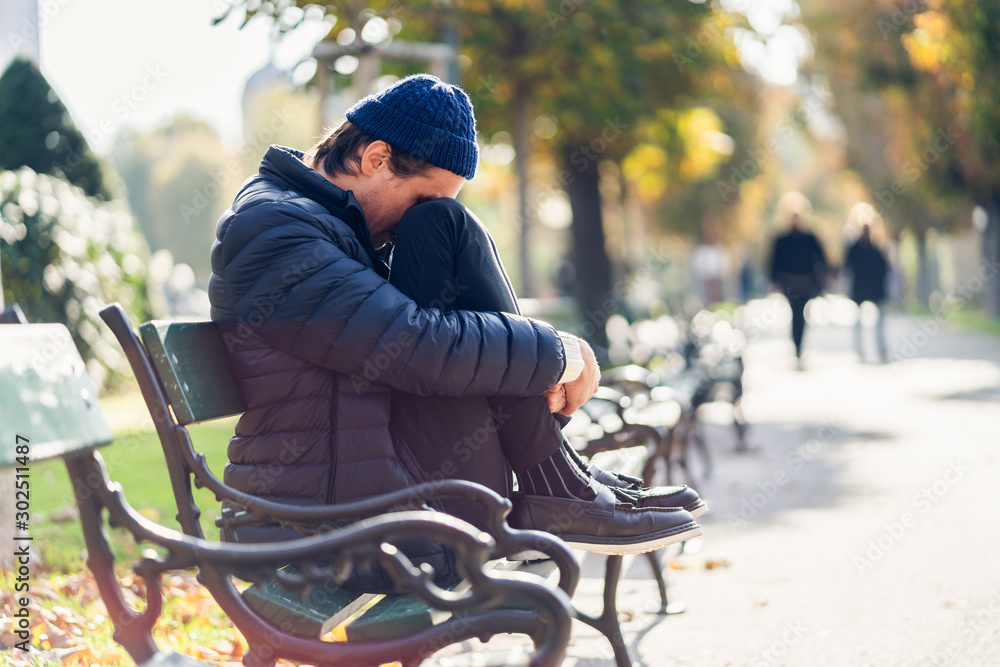 Fototapety, obrazy: Worried young man on a bench during autumn day