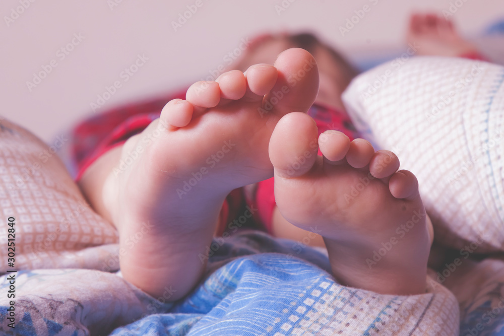 Fototapety, obrazy: Little child girl sleeping in bed at home. Feet under the blanket on her bed on bedroom. Holiday, sleep and relax concept.