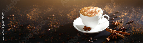 Obraz White cup with coffee on a black background, top view. Coffee with cinnamon. Long banner with copy space. Macro photo. - fototapety do salonu