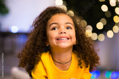 Fotomural  Cheerful afro girl portrait near Xmas tree