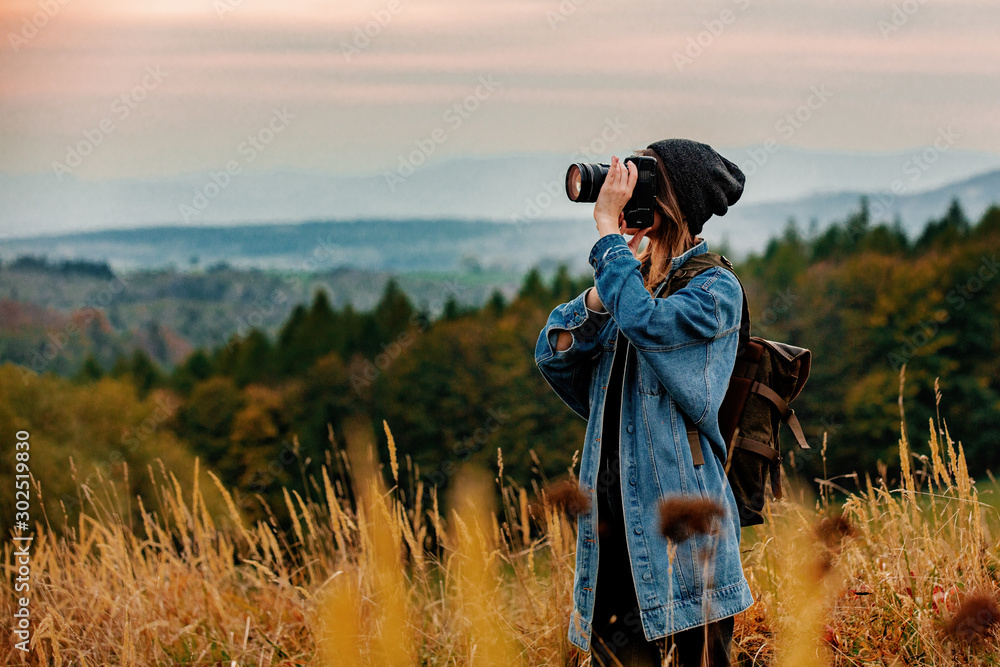 Fototapety, obrazy: Style girl with camera and backpack at countryside with mountains on background