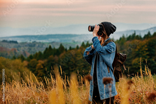 Obraz Style girl with camera and backpack at countryside with mountains on background - fototapety do salonu