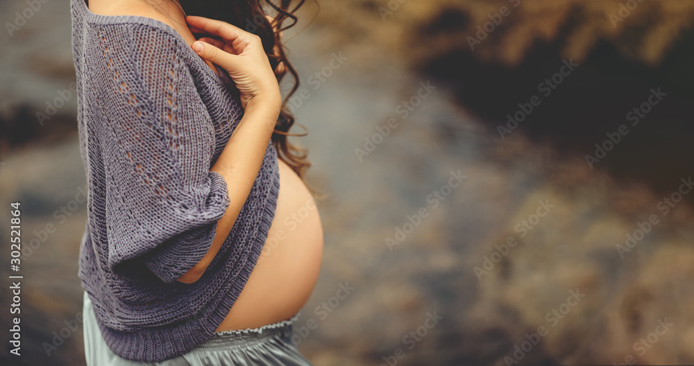 Fototapeta Cute pregnant belly outside. Young pregnant woman embracing her naked abdomen with hands outdoor. Big belly on the third trimester of pregnancy close-up. Concept of happy pregnant life.