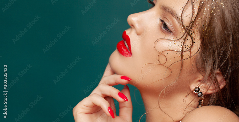 Fototapety, obrazy: Close-up portrait of beautiful woman with holiday make-up. Perfect red lips and nail design. Gold glitters on her face. Christmas make-up