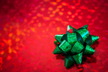 Christmas Present Wrapped In Sparkling Red Holiday Paper Topped By A Shiny Green Bow