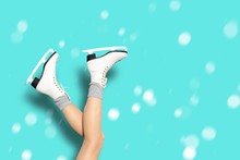 Sexy Woman Legs Wearing Ice Skates And Woolen Socks Over Blue Background With Snowflakes