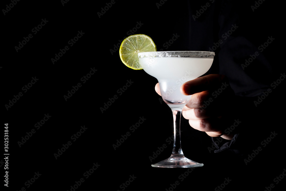 Fototapeta bartender serves a classic margarita with lime, he holds a cocktail in his hand on a black background