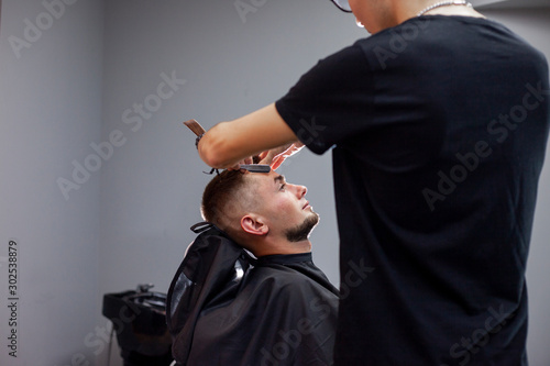 Valokuvatapetti Kazakh barber shaves beard with a razor to a client in a barbershop, a young guy