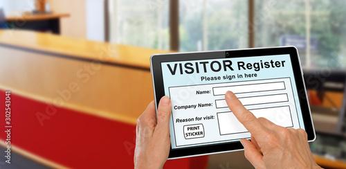 Obraz na płótnie Visitor completing a sign in register form on computer tablet