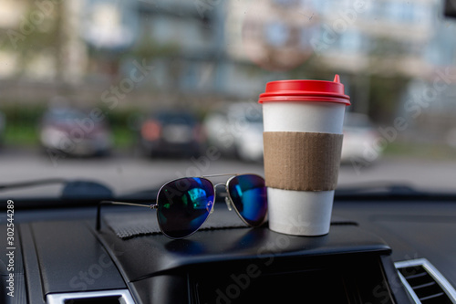 Recess Fitting Tea White paper coffee Cup and sunglasses on the dashboard of the car. Paper Cup with hot tea and glasses on the dashboard of the SUV close up against the background of a blurred Parking lot
