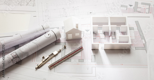 Fototapeta Construction concept. Residential building drawings and architectural model, obraz