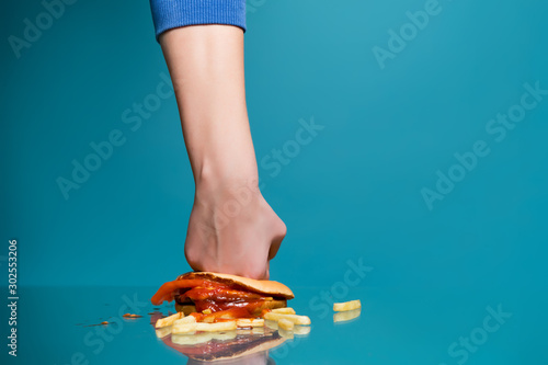 Fototapeta  girl smears a burger with his fist on a glass table