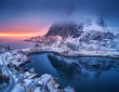 canvas print picture - Aerial view of snowy mountain, village on sea coast, colorful sky at sunset in winter. Top view of Reine, Lofoten islands, Norway. Moody landscape with high rocks, houses, rorbu, reflection in water