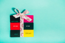 Top View Colourful Shop Gift Cards In Shape Of Present Box With A Bow Of Satin Ribbon On Bright Turquoise Background. Creative Ideas For Presents. Flat Lay. Holiday Sales Mockup With Copy Space.