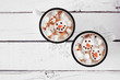 canvas print picture - Two cups of holiday hot chocolate with snowman marshmallows. Top view on a white wood background.