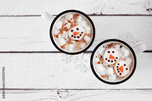 Obraz Two cups of holiday hot chocolate with snowman marshmallows. Top view on a white wood background. - fototapety do salonu