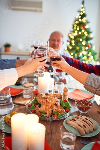 Beautiful family meeting smiling happy and confident. Eating roasted turkey toasting with cup of wine celebrating Christmas at home - 302559605
