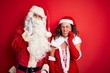 canvas print picture - Middle age couple wearing Santa costume and glasses over isolated red background touching mouth with hand with painful expression because of toothache or dental illness on teeth. Dentist concept.