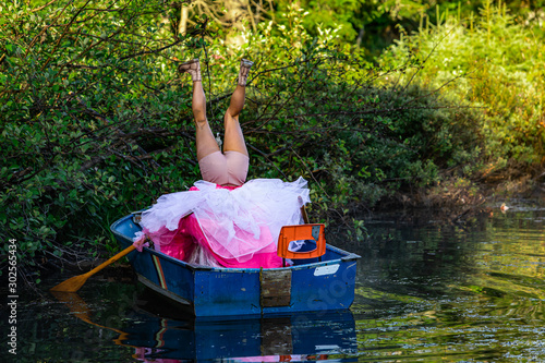 Foto Behind view of a person in a small wooden boat on water making strange upside do