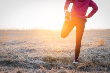 Adult fitness sportswoman runner stretching legs before run on field.