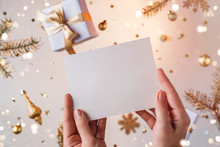 Female Hands Holding A Letter To Santa On Light Golden Background With Flying Christmas Decorations, Fir Branches, Balls, Sparkles And Confetti. Xmas And New Year Holiday, Bokeh, Light.Selective Focus