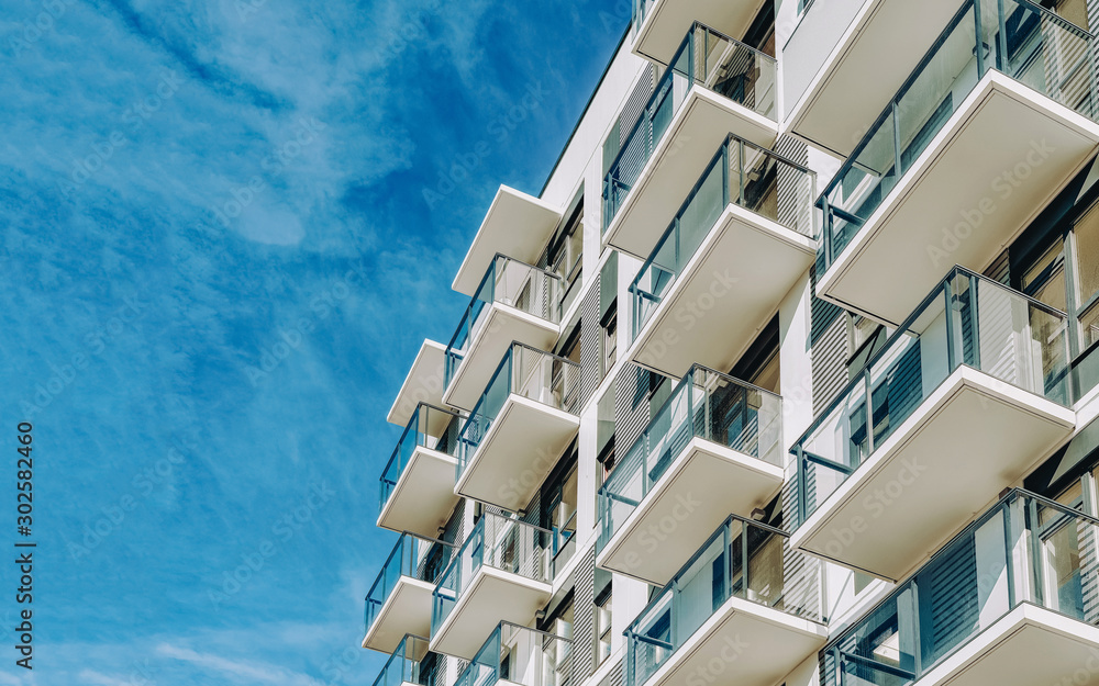 Fototapeta Detail of Modern residential apartment flat building exterior. Fragment of New luxury house and home complex. Part of City Real estate property and condo architecture. Copy space. Blue sky
