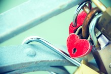 Close Up Of Heartshaped Love Padlock Locked On The Rail Of A Bridge -  A Symbol And A Promise For Eternal Love