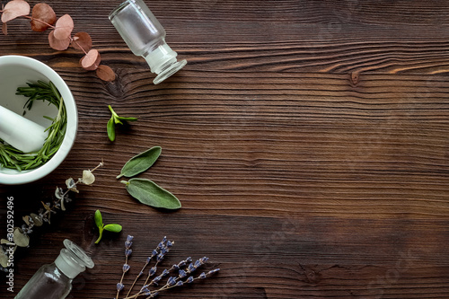 Obraz Apothecary of natural wellness and self-care. Herbs and medicine on dark wooden background top view frame copy space - fototapety do salonu