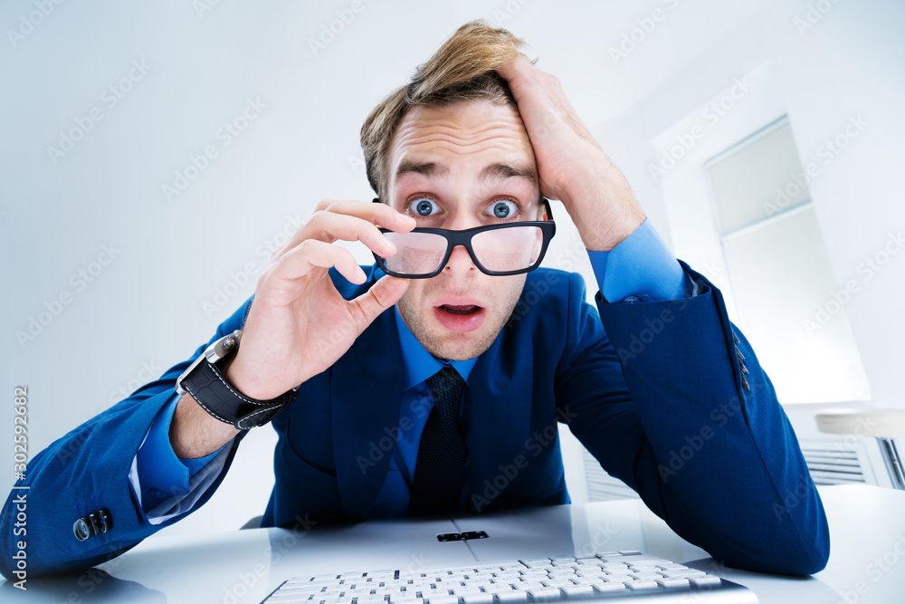 Fototapeta Shocked or surprised confident businessman in blue suit and glasses, working with computer at office. Success in business, job and education concept.