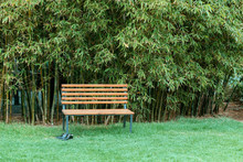 A Wooden Bench And Black Shoes Against Bamboo Background.