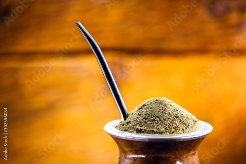 Yerba mate tea in wooden bowl on wooden table. Traditional drink from Brazil, Argentina, Paraguay and South America.