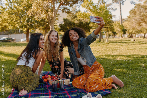 Fotografia Group of happy diverse three female friends sitting together on blanket over the