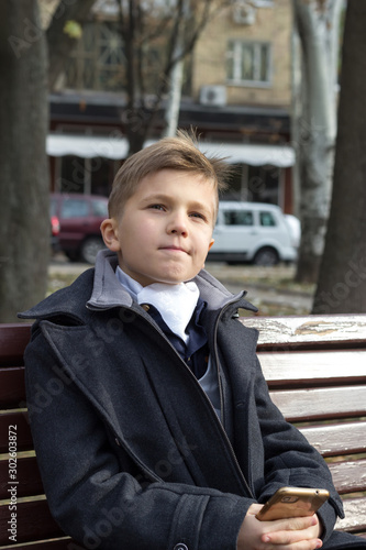 Photo A boy sits on a bench in a park in business clothes with an appraising look and a slight smile