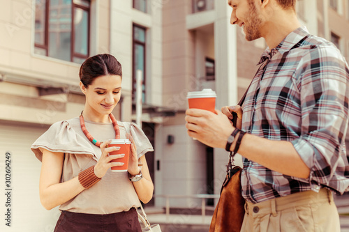 Kind young female person staring at her paper cup