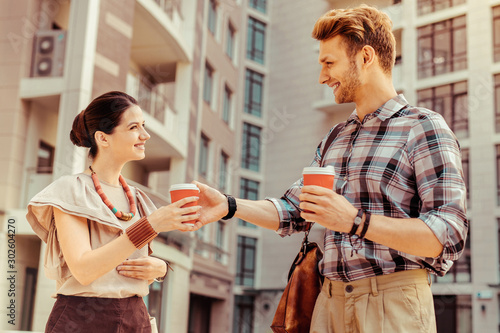 Positive delighted young man giving coffee to his friend