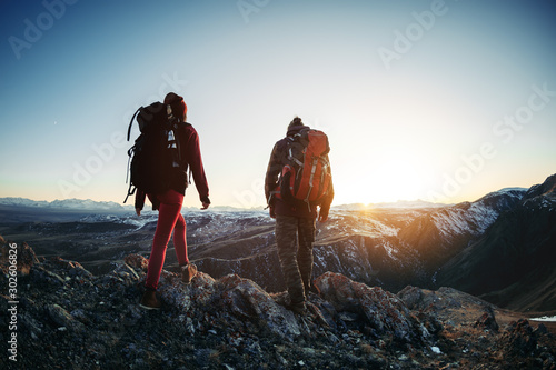 Obraz na plátne Two hikers walk sunset mountains