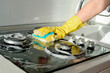canvas print picture - A hand in a yellow rubber glove washes a gas stove on a sunny day. Kitchen cleaning