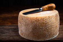 Hard Cheese Wheel Matured In Diary Cellar With Cheese Knife