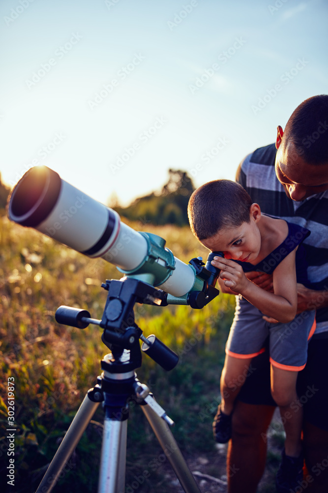 Fototapety, obrazy: Father and son observing the sky with a telescope.