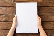 Overhead Shot Of Woman's Hands Holding Blank Paper Sheet On Rustic Wooden Table. Close Up
